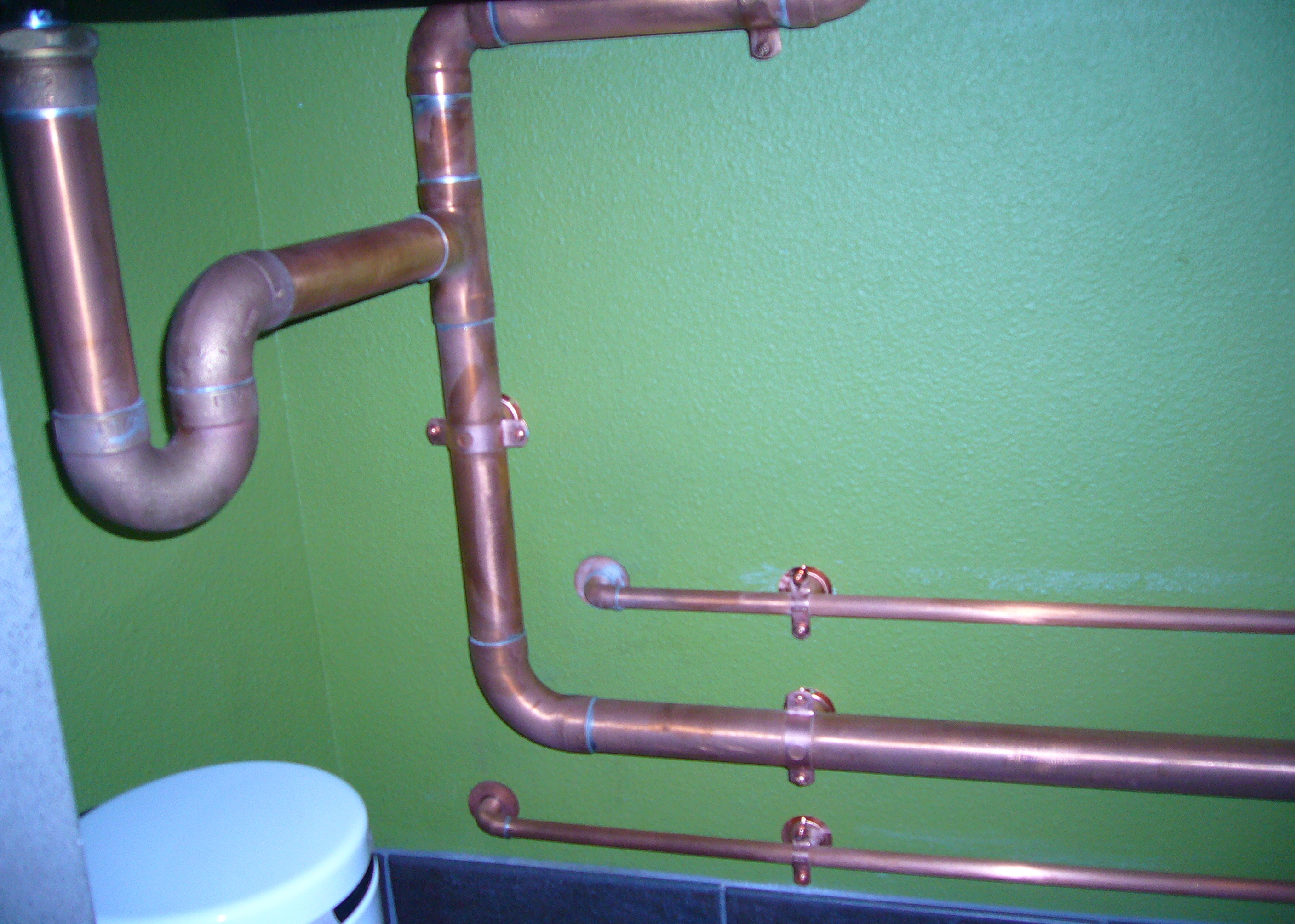 under sink copper ptrap drain lines and water lines attached to wall with copper bell hangers